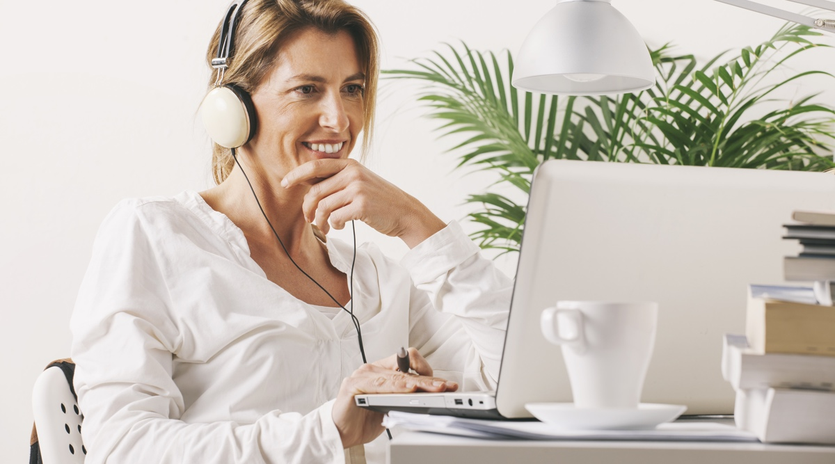 Mature lady sitting relaxed with a laptop and headphones